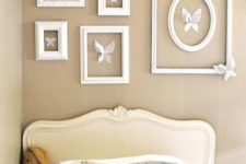 a gallery wall of empty frames with white paper butterflies is a cool idea to make your vintage space more refined