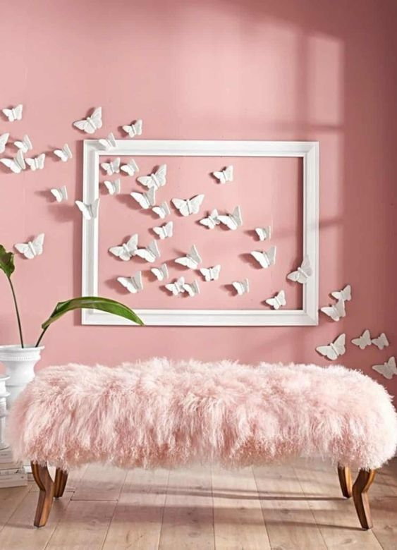 a girlish space with a pink wall spruced up with a white fframe and white 3D butterflies on the wall