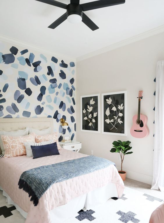 a guest bedroom with an abstract bright wallpaper wall with brushstrokes for a bold accent