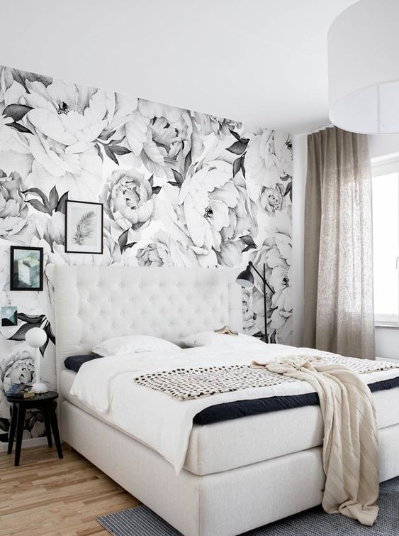 a monochromatic bedroom with a floral print wall that adds a bold print touch to the space