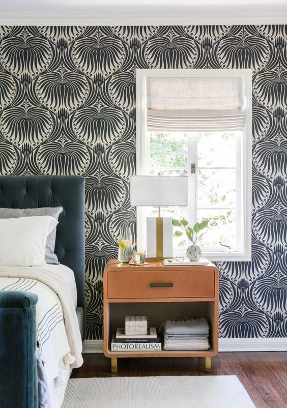a monochromatic bedroom with a printed wallpaper wall that adds pattern to the space