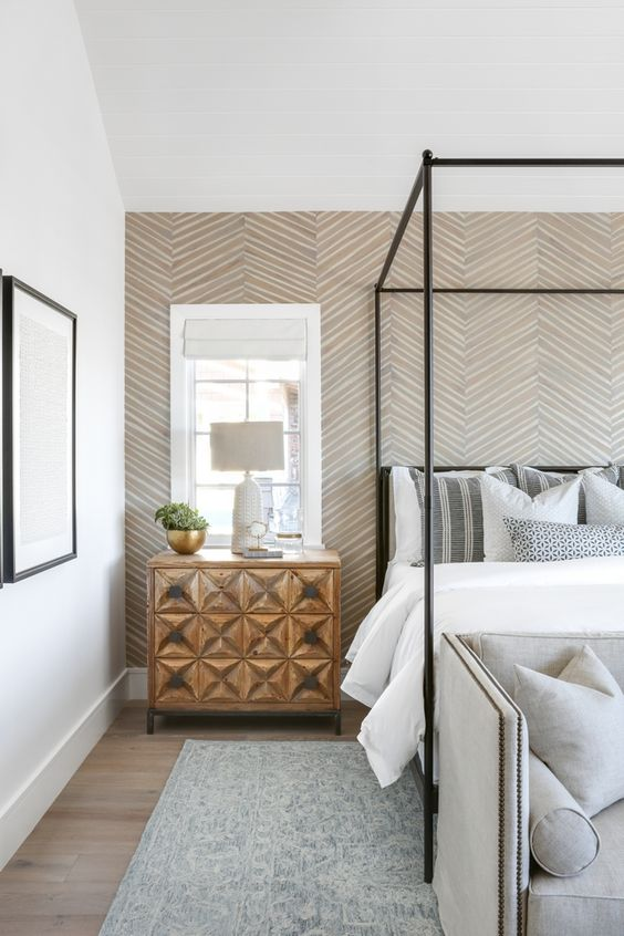 a neutral bedroom with a geometric print wallpaper wall that accents the space with pattern and colors