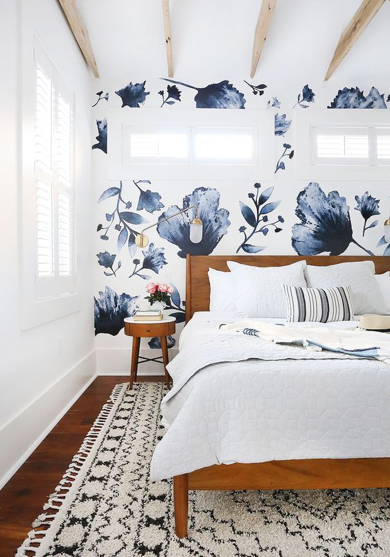 a neutral bedroom with a navy and white floral print wall that adds catchiness and makes the space bold