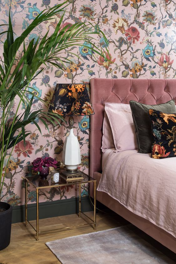 a pink floral wallpaper continues the theme of the bedroom and adds whimsiness to the space