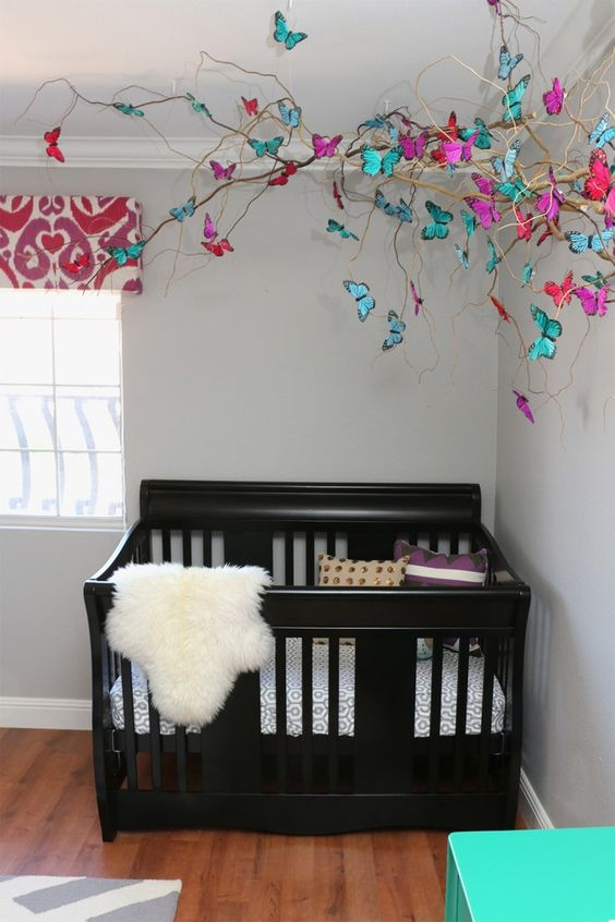 a whimsical decoration of branches and colorful paper butterflies for sprucing up a girl's nursery