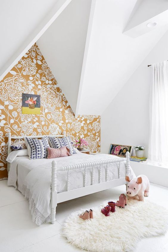 an attic bedroom with a mustard floral print wall for a touch of color and pattern in the space
