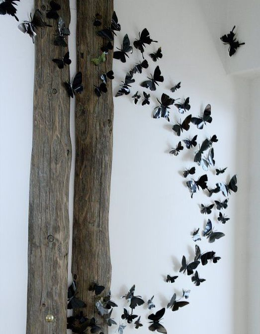 whimsical wall decor of reclaimed wood and 3D black butterflies that are attached to the wall