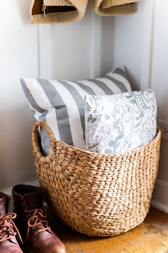 a basket with printed pillows is a nice addition to a living room or another space