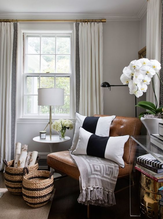 a cute nook with a leather chair, some orchids and matching striped baskets for storage
