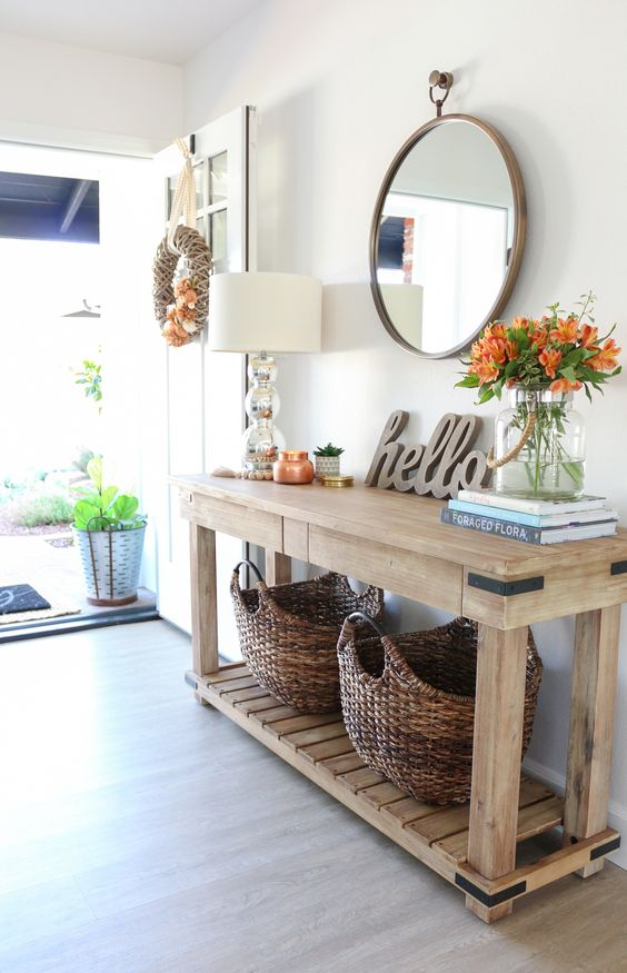 a farmhouse entryway with a wooden console table and baskets for storage, bright blooms and a round mirror