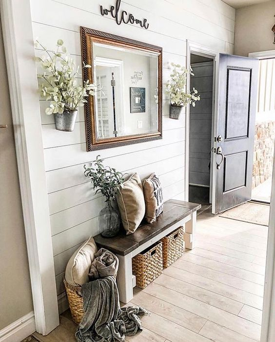 a neutral farmhouse entryway wiht a wooden bench and wicker cubbies plus a basket for storage