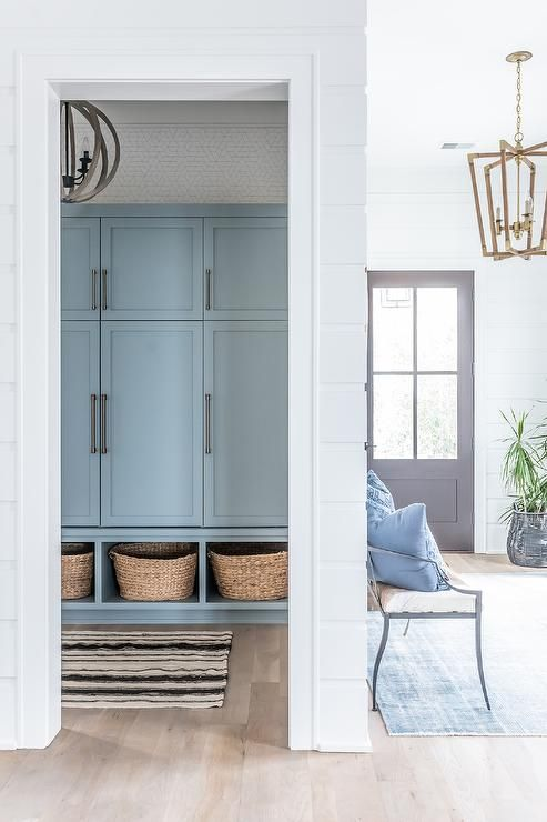 a powder blue wardrobe in the entryway zone finished off with wicker cubbies for small storage