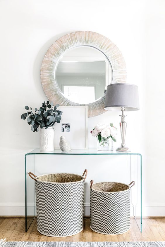 a sheer acrylic console, a couple of patterned baskets for storage, a wood clad mirror and a chic lamp