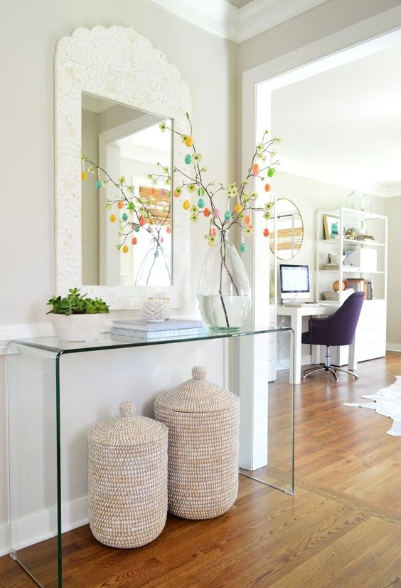 a sheer acrylic console table, matching baskets with lids for storage and a planter with succulents