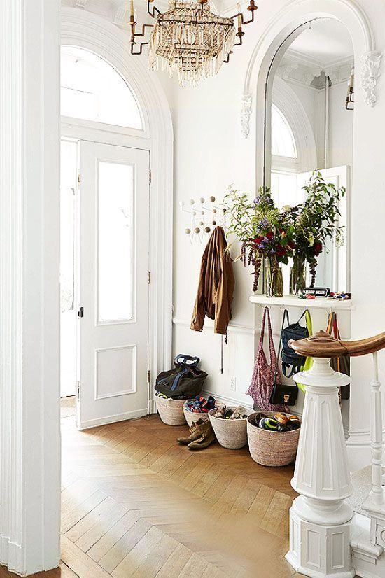 a traditional entryway with wicker basket storage, a statement mirror and a vintage chandelier looks cool