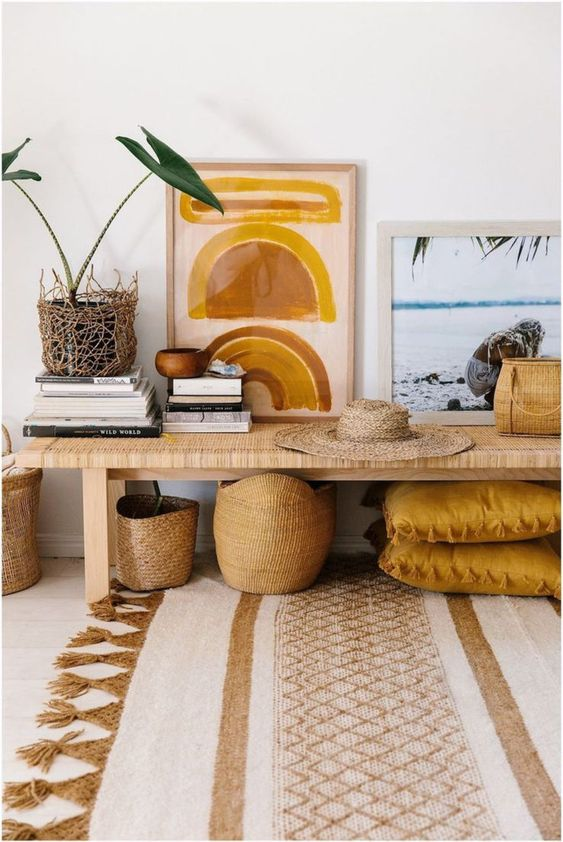 a tropical entryway with a wicker bench, some baskets for storage, a potted plant and cool artworks
