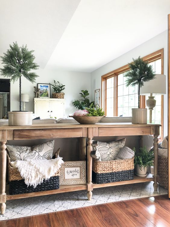 a wooden console table with matching wicker cubbies with blankets and pillows is a cool idea