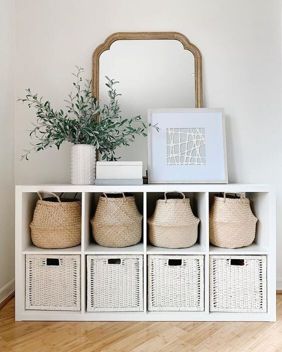 an entryway console table with baskets and white wicker cubbies allows storage without cluttering