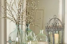 a blue and green bottle with blooming branches make up a cool spring-infused decoration