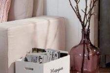 a brown vintage bottle with some branches add a cute and cool touch of spring to the space