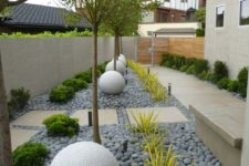 a chic and manicured backyard done with grey pebbles, greenery and large stone balls
