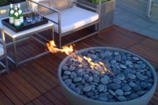 a concrete fire bowl with grey pebbles looks very contemporary and makes your space very cozy