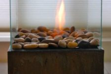 a contemporary metal and glass fireplace with pebbles for decor looks modern yet natural