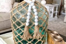 a green bottle with a twine net and whitewashed wooden beads is a cool decoration for a modern space