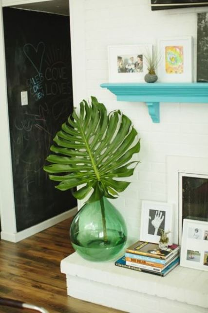a green bottle with an oversized tropical leaf brings a bold touch of color to the space and makes it fresher