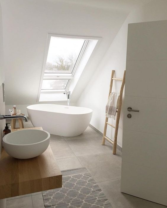 a minimalist attic bathroom with grey tiles, white walls, a floating vanity, a round sink, wooden furniture and a rug