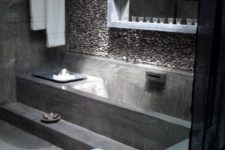 a minimalist concrete bathroom done with a single pebble covered wall for a natural feel