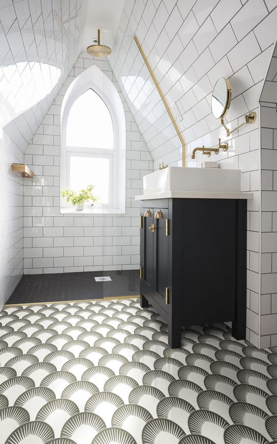 a monochromatic art deco attic bathroom with white and black tiles, a catchy printed floor, touches of gold for more chic