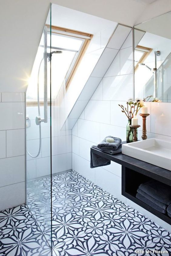a monochromatic attic bathroom with large scale white tiles and floral print ones, with a skylight and a shower space
