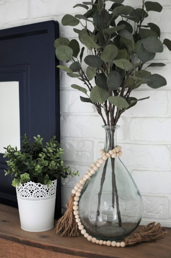 a pretty decoration of a vintage bottle, with green branches and wooden beads brings a lively feel to the space