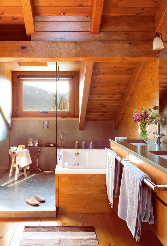 a rustic attic bathroom all clad with amber-stained wood, with a small window, a concrete shower space is very chic
