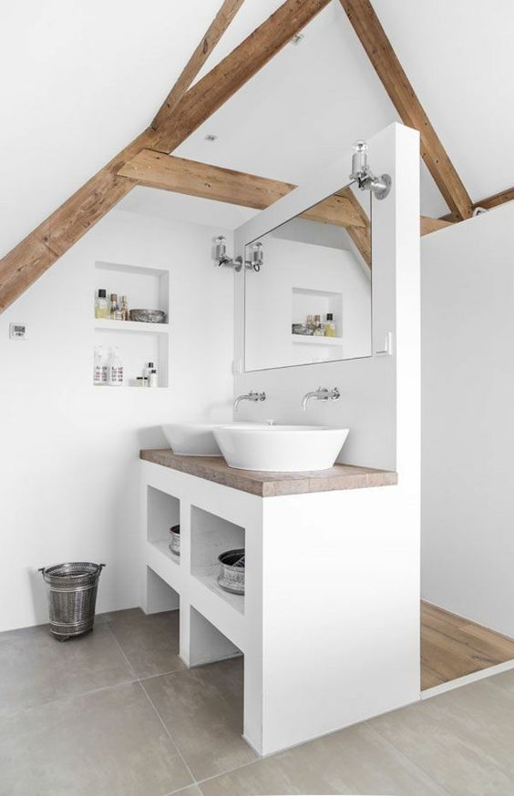 a small attic bathroom in white, with grey tiles, wooden beams, a vanity that separates the spaces and much storage space