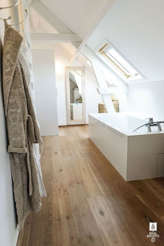 a small contemporary attic bathroom in white and light-stained wood, with windows and a large tub