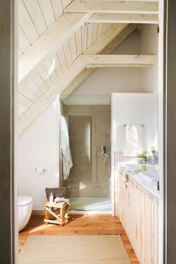 a small light rustic attic bathroom with much painted and stained wood, neutral tiles in the shower and wooden furniture