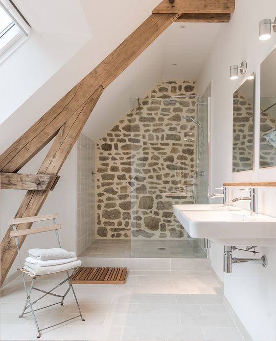 a small rustic attic bathroom with a stone wall, a wooden beam, a folding chair and a sink