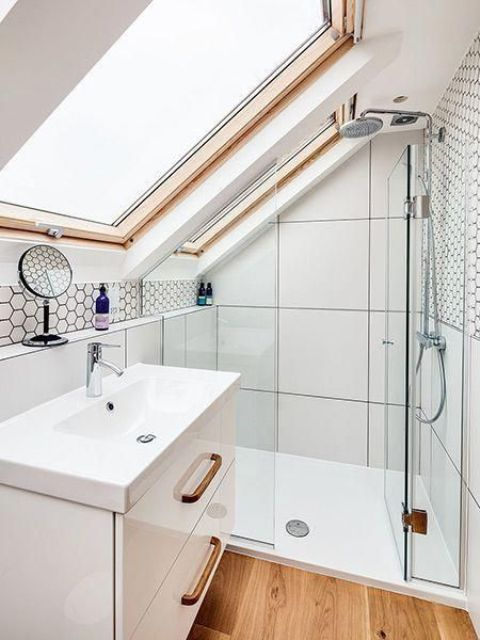 a small white attic bathroom with windows, a shower space, a compact vanity and a sink looks super chic