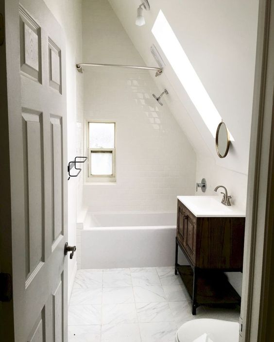 a small yet elegant white attic bathroom with various white tiles here and there, a dark vanity, a skylight for a natural feel
