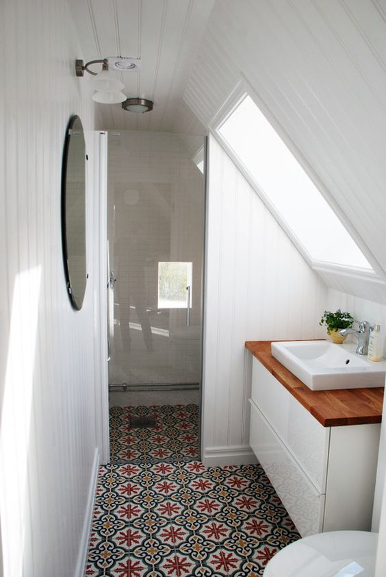 a tiny attic bathroom with a printed tile floor, white paneling on the walls, a white vanity and two windows