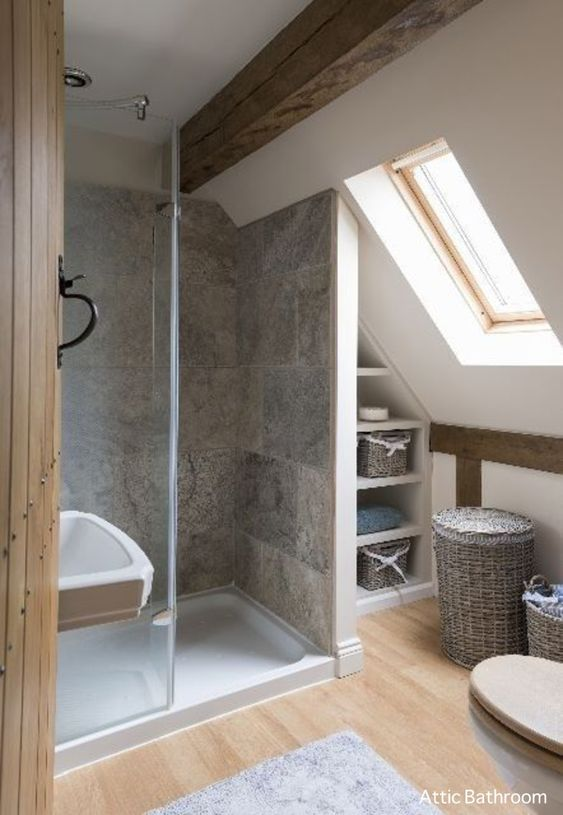 a tiny attic bathroom with a skylight, wooden beams, grey tiles and baskets for a cozy rustic feel