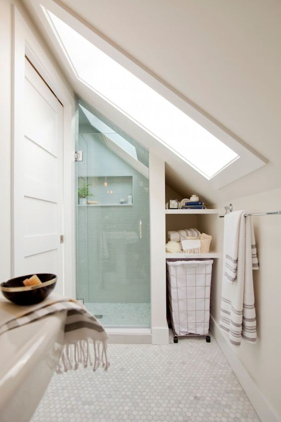 a tiny contemporary attic bathroom with mother of pearl hex tiles, a shower with a skylight and some storage space