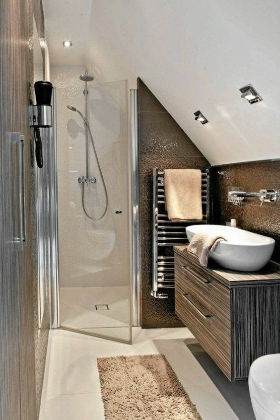 a tiny modern attic bathroom done with shiny dark tiles and neutral ones, with a shower and a floating vanity