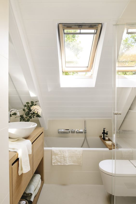 a tiny neutral bathroom with white and tan tiles, a skylight, wooden furniture and white appliances looks chic