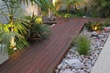 a tropical garden with pebbles covering the greenery and a rich-stained wooden pathway