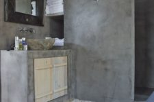 a wabi-sabi bathroom done with concrete and a pebble floor plus a stone sink is a bold and catchy idea