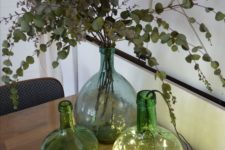 an arrangement of green bottles with lights, with dried eucalyptus is a cool decoration idea for your space