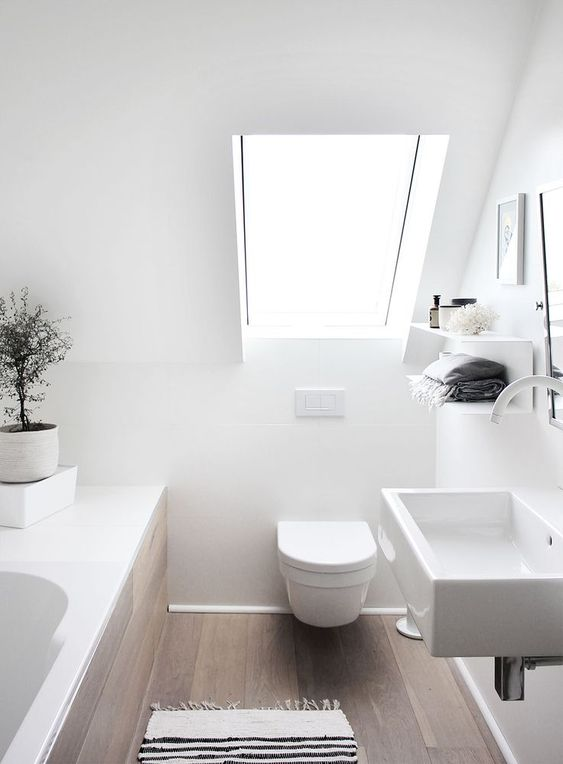 an attic Scandinavian bathroom in white, with stained wooden floor, white appliances and a skylight is airy and serene